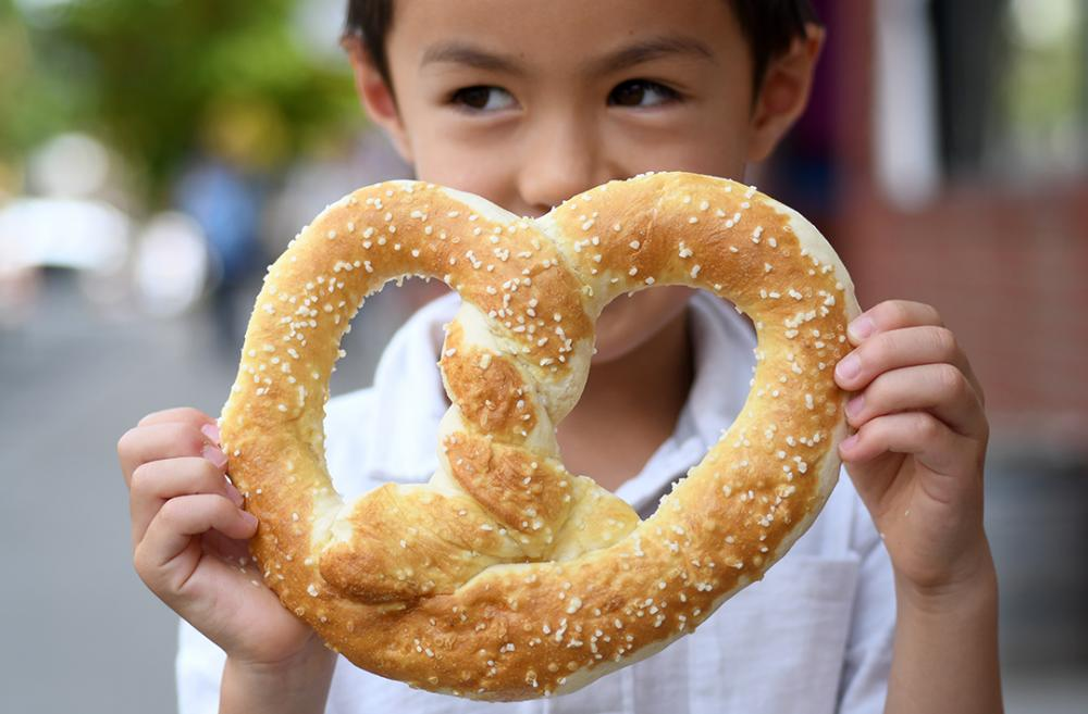 Boy-eating-giant-pretzel-Leavenworth-Washington-perfect-fall-family-getaway-destination-Seattle