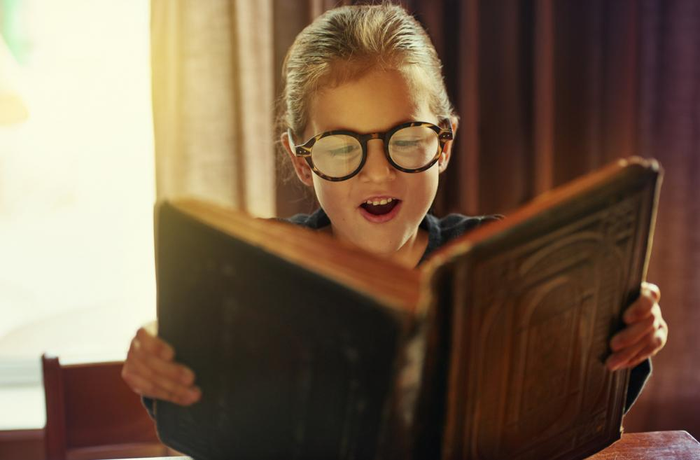 Young boy wearing glasses reads a magical book