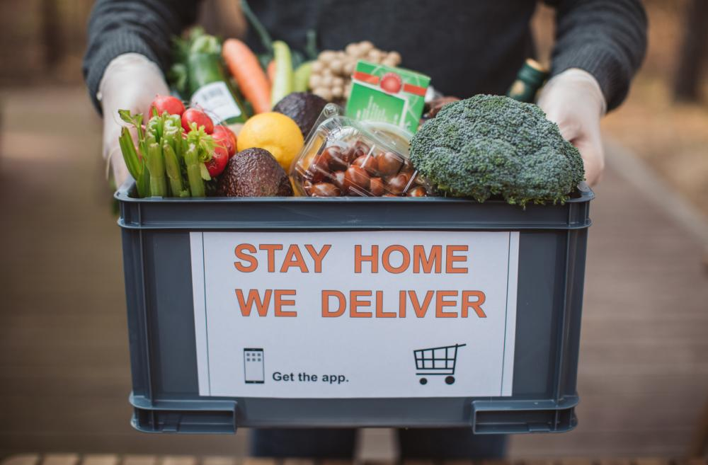 plastic crate full of food with the words 'stay home we deliver' on the front