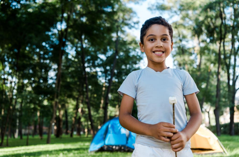 boy holding a marshmallow on a stick with two tents in the background
