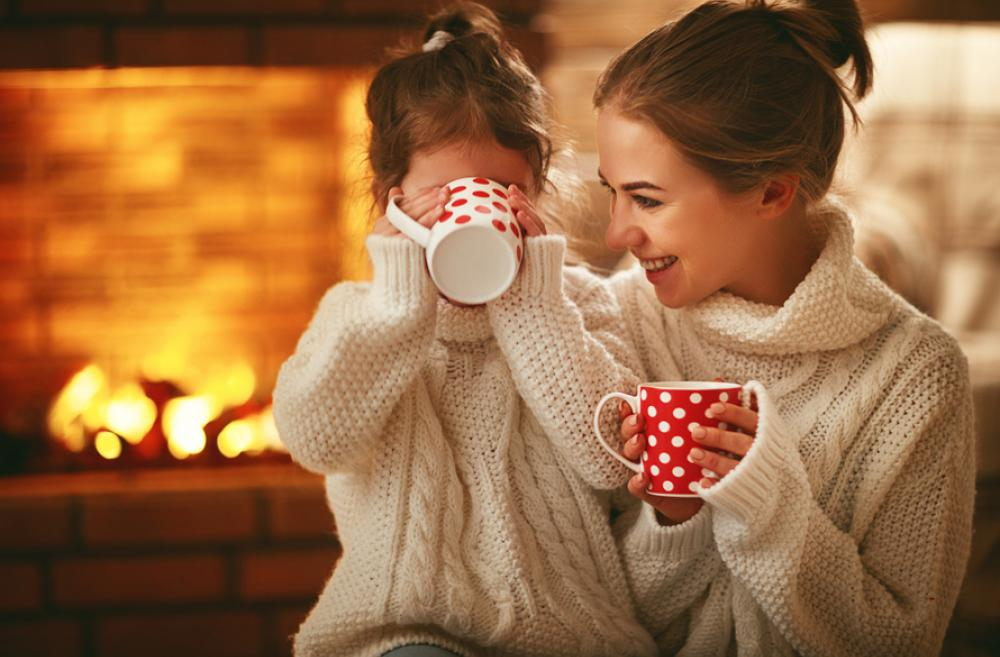 mother and daughter drinking hot cocoa in front of a fire