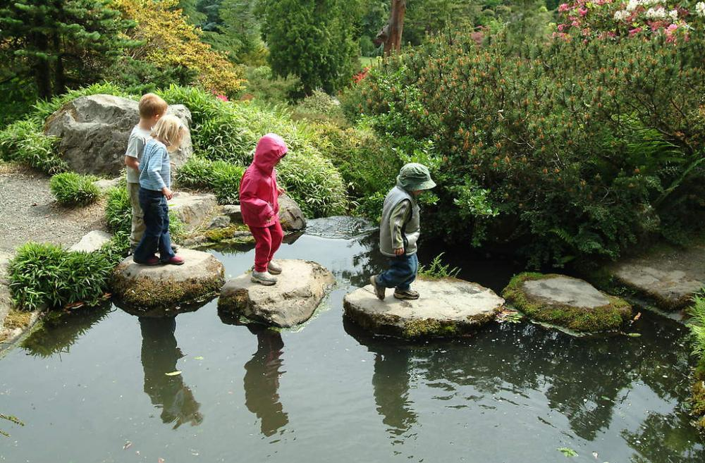 Kids crossing a pond on stones, wearing jackets, at Kubota Garden Seattle urban garden city park
