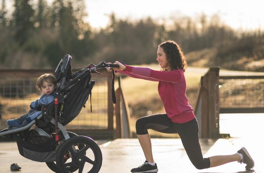 Mom young child in running stroller doing a lunge for exercise on best paths and trails for kids and strollers around Seattle and the Eastside