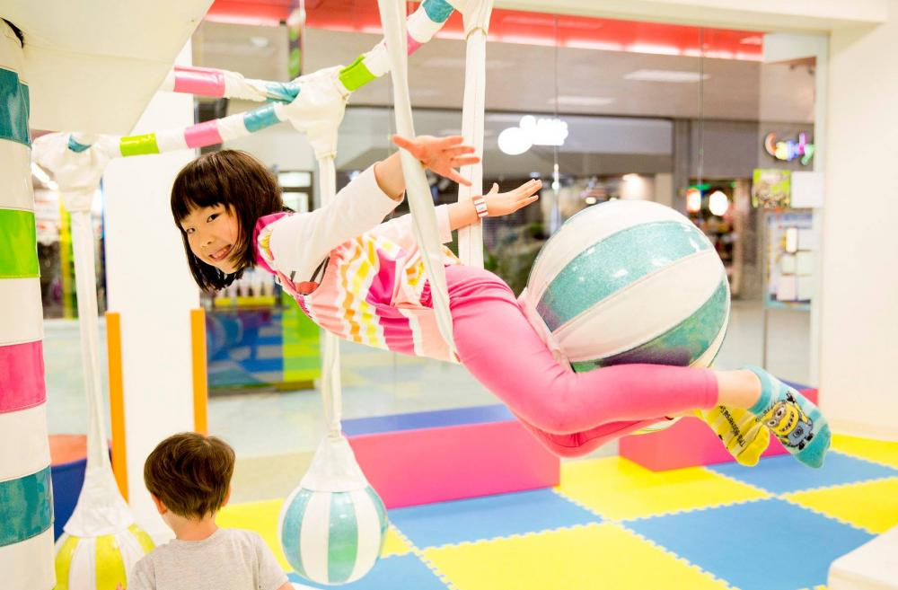 Young girl plays on soft-sided tot and preschool gym equipment at WiggleWorks Kids a