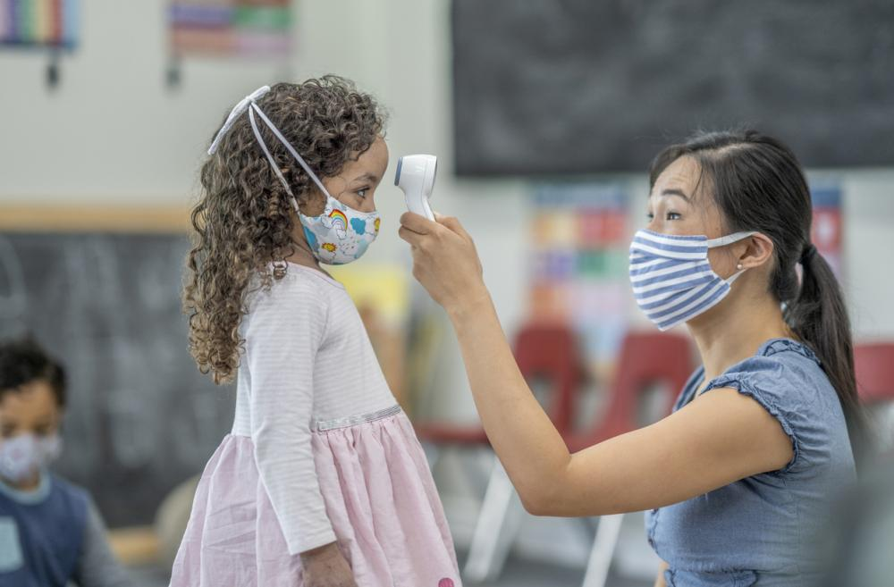 daycare woman in a mask taking a child's temperature