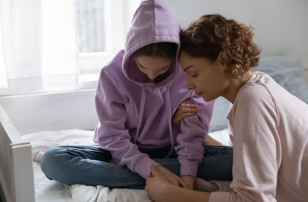 mother comforting a sad-looking teen wearing a hoodie