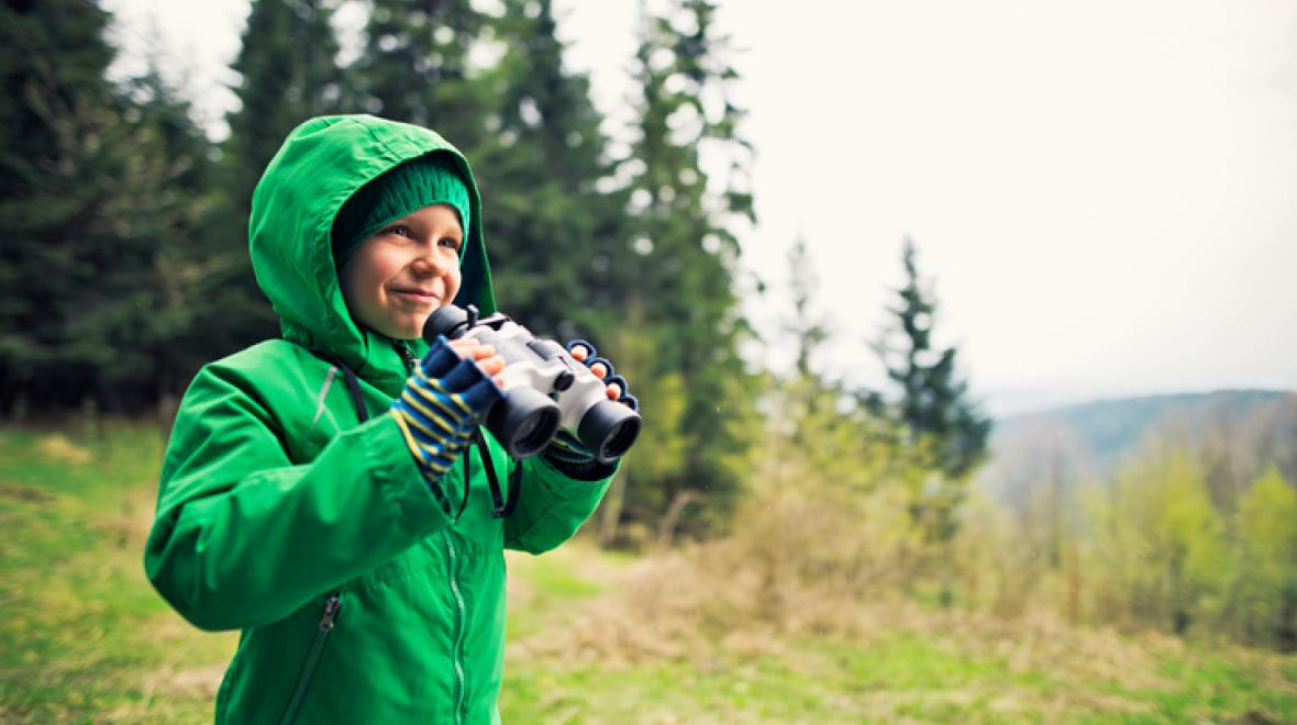 Boy in green raincoat outdoors