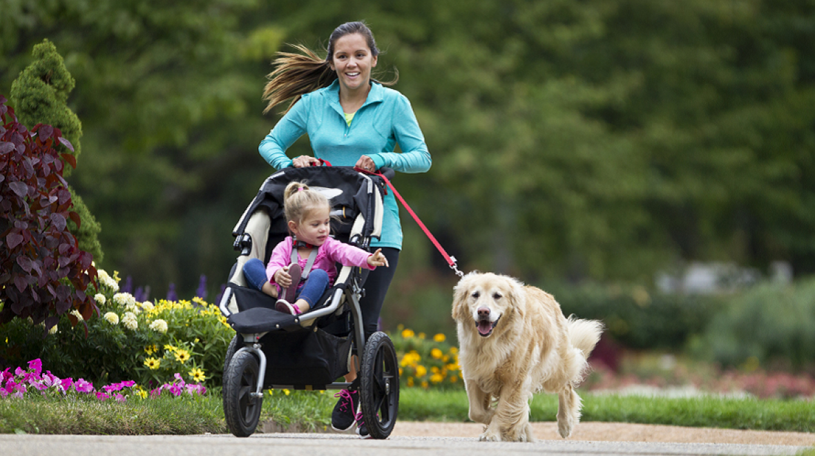 Mom running with child in stroller and dog