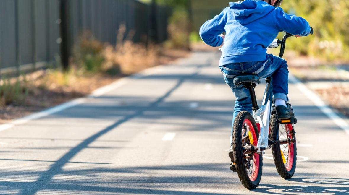 Boy learning to bike on a bike path