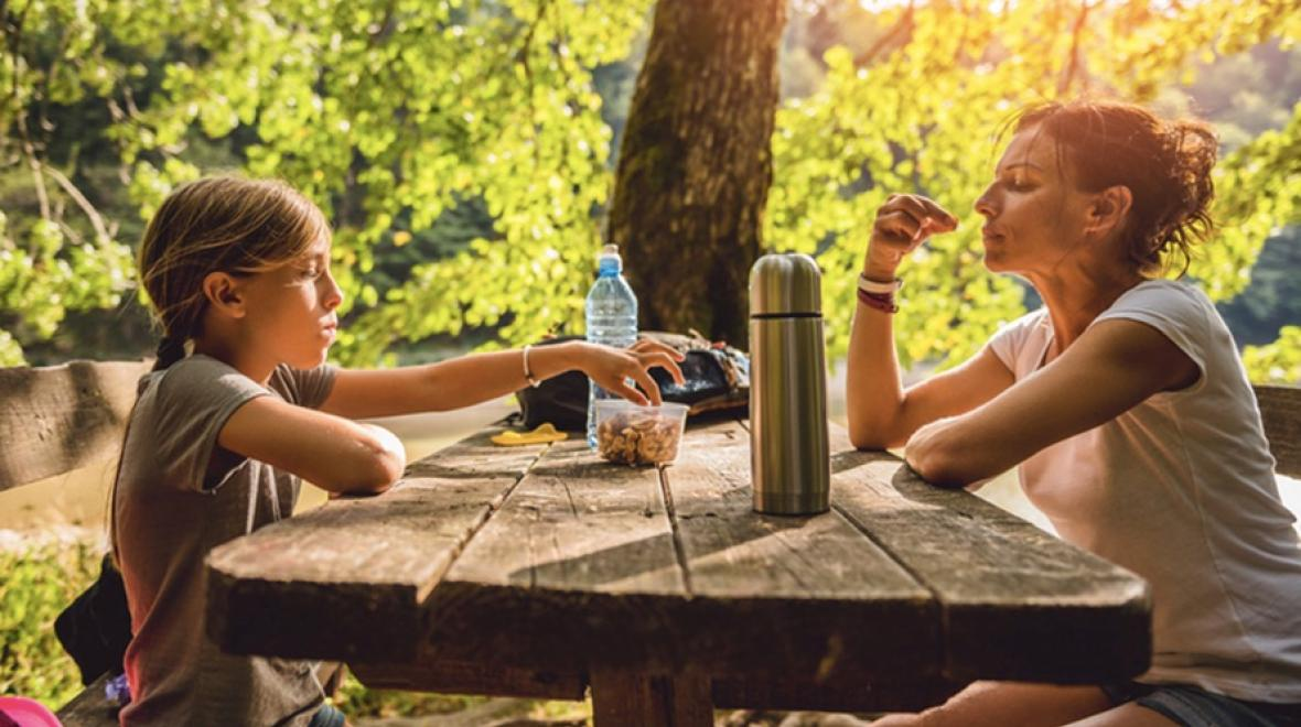 Parent and child eating while camping or hiking