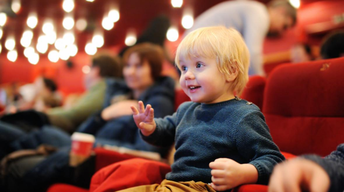 little boy at the theater enjoying a performance