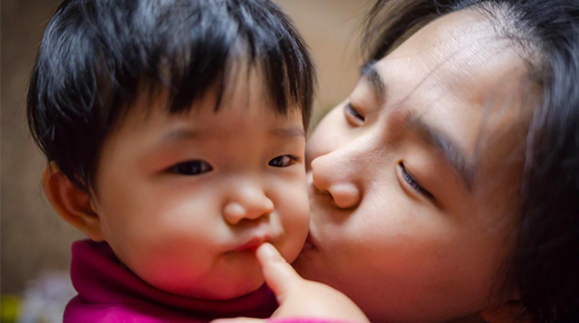Mom kissing child's cheek