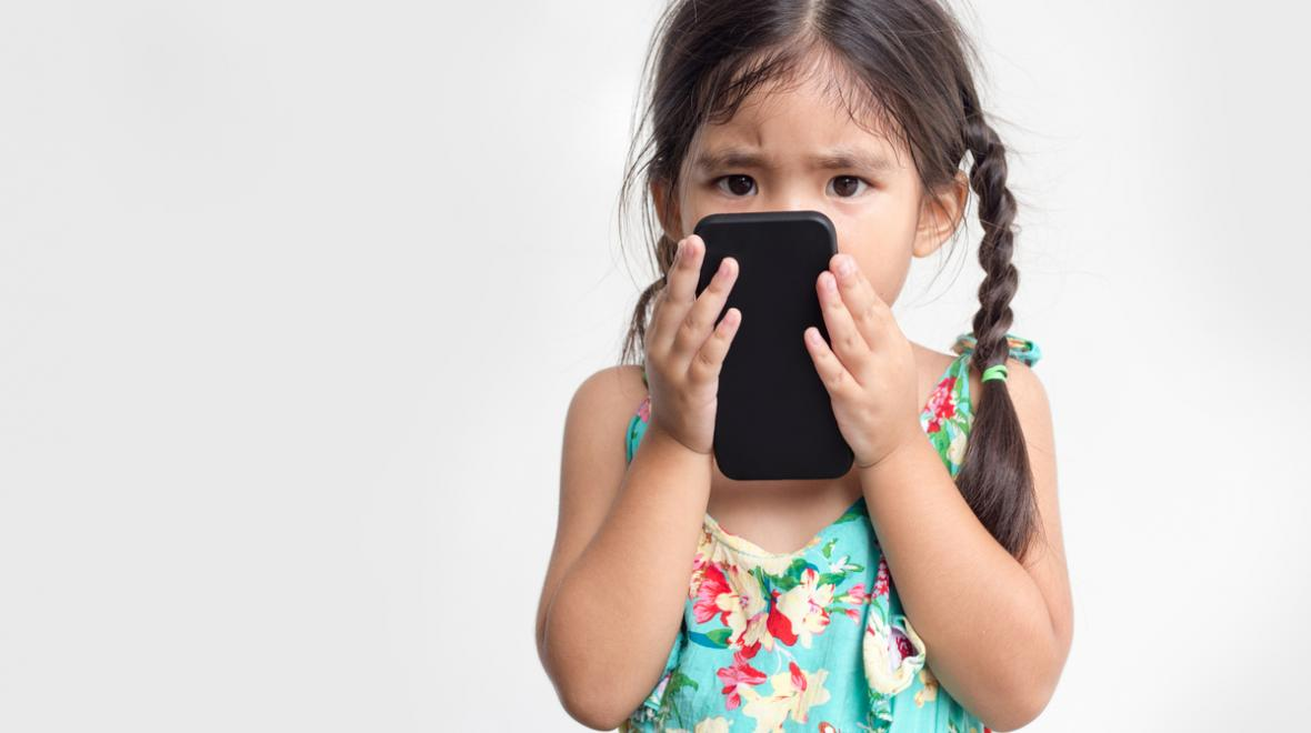 Young girl holding a phone close to her face