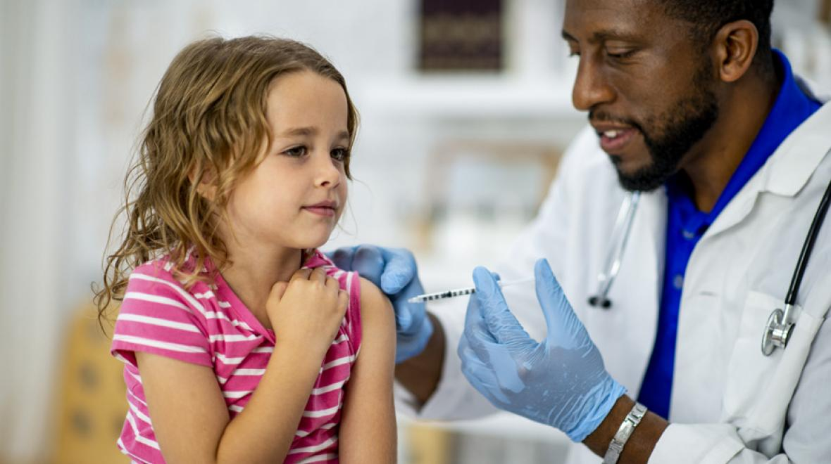 doctor giving girl a vaccination