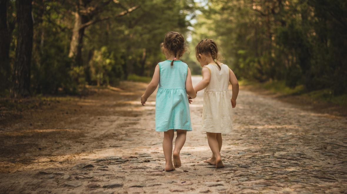 Twin girls walking down a dirt road