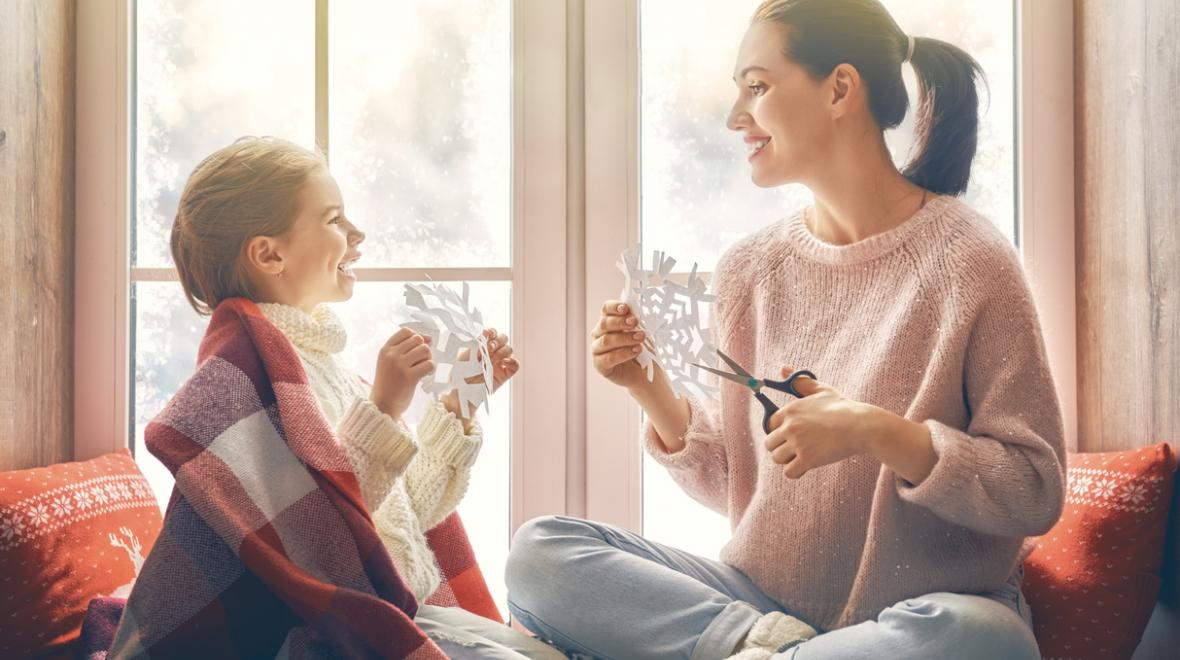mother and daughter relaxing making paper snowflakes craft