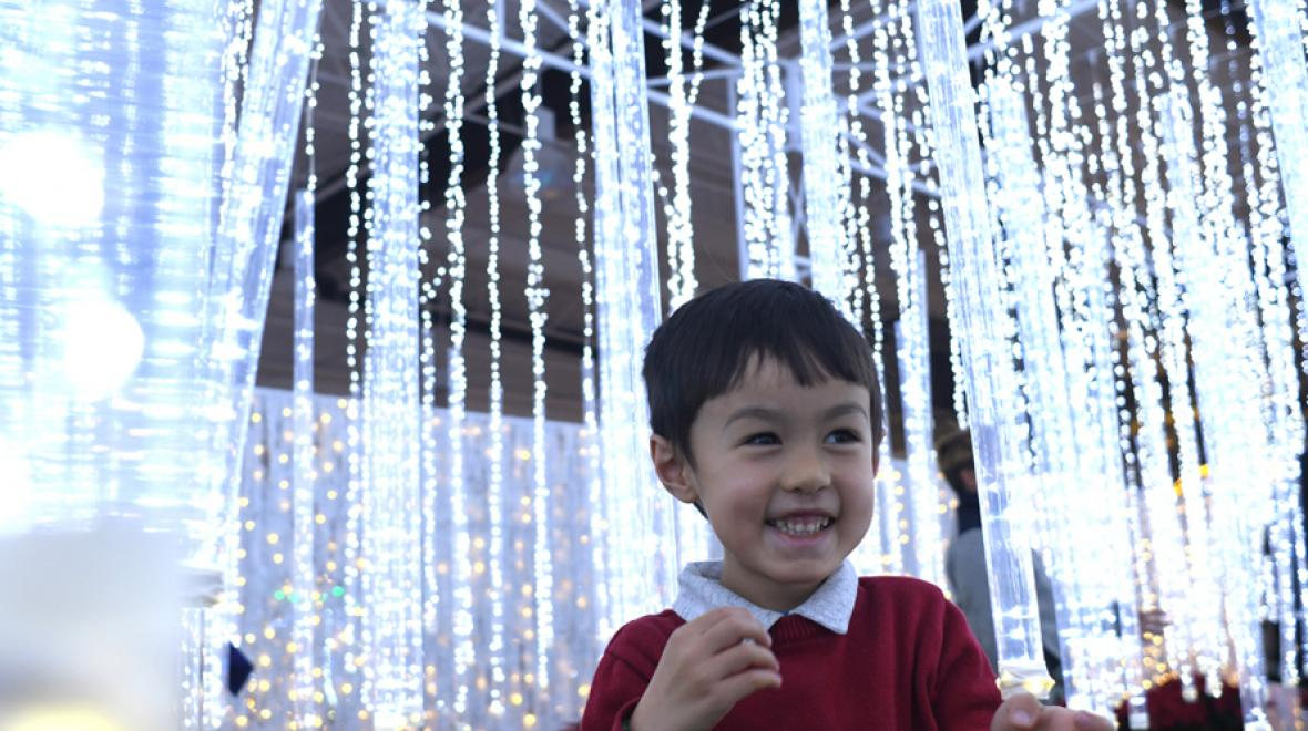 little boy smiling with glittering lights behind him