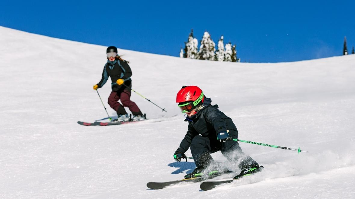 Child and parent skiing at SilverStar Mountain Resort, B.C., Canada