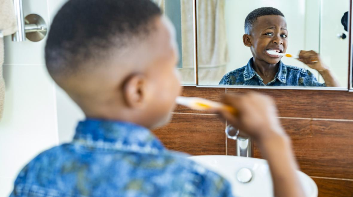 little boy brushing his teeth in front of the mirror