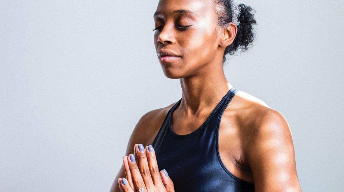 woman meditating with hands together and eyes closed