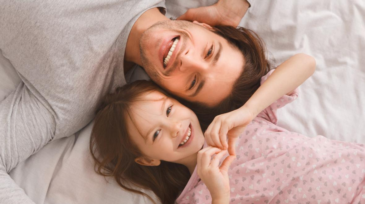 father and daughter lying down smiling at the camera