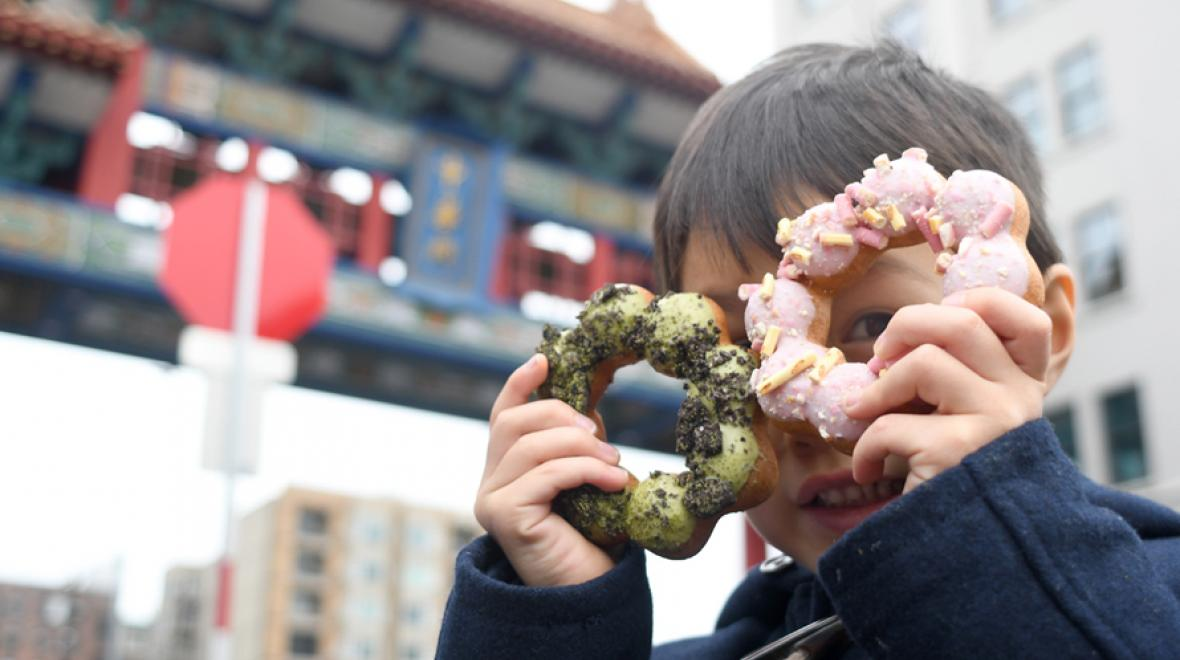 kid holding dochi mochi doughnuts up to his face