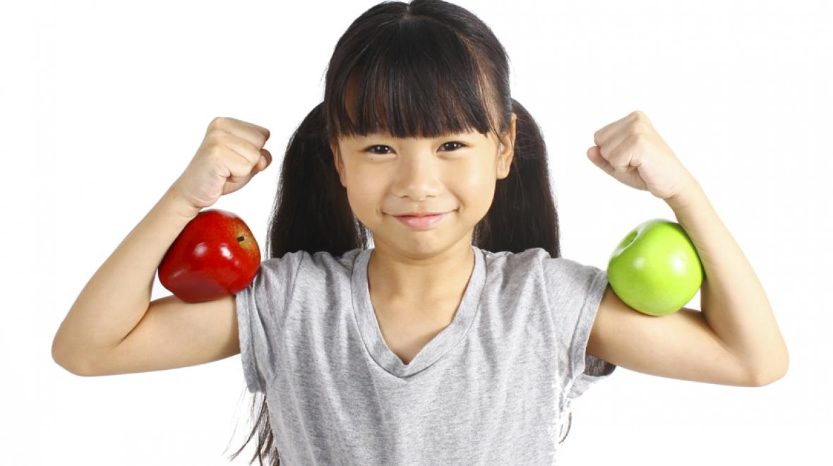 little girl holding her arms up to show off her biceps, with apples balanced on her arms
