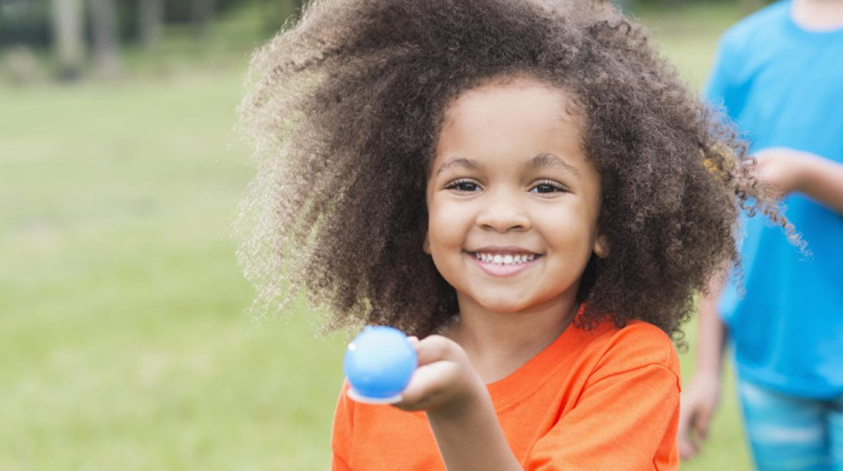 little kid holding a blue egg on a spoon outdoors