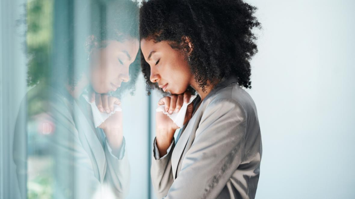 frustrated woman leaning against a window having a moment to herself