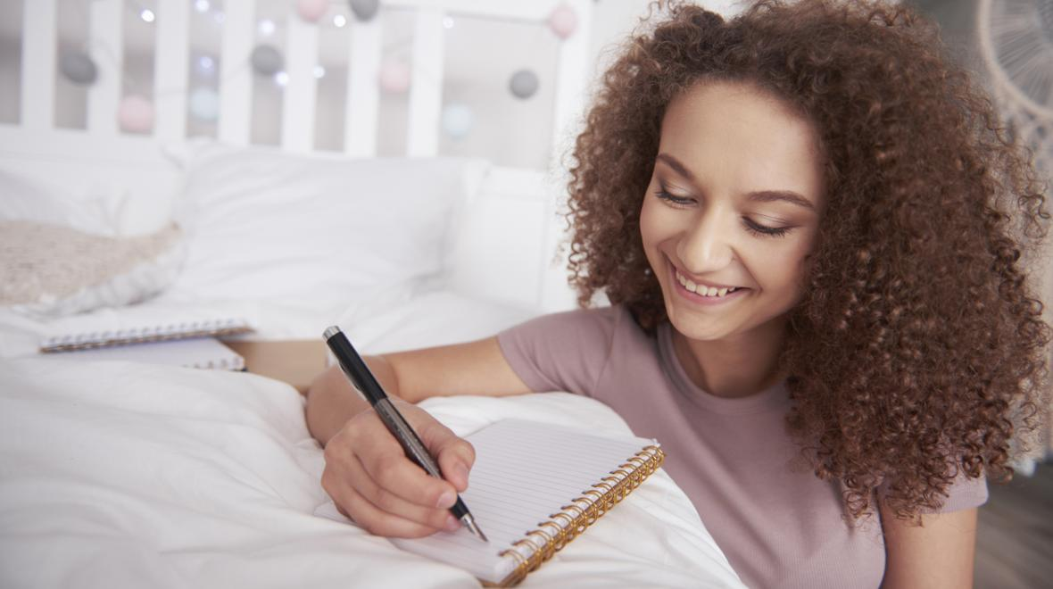 teen girl writing in a notebook on her bed