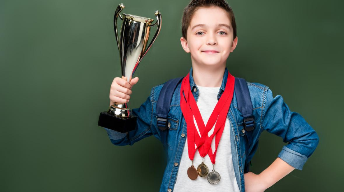 boy holding a trophy with gold medals around his neck