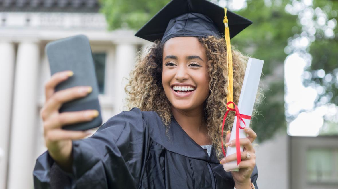 girl in a cap and gown taking a selfie at graduation 2020