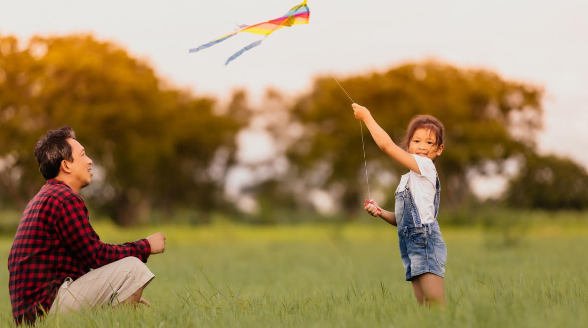 dad and daughter flying a kite in a field