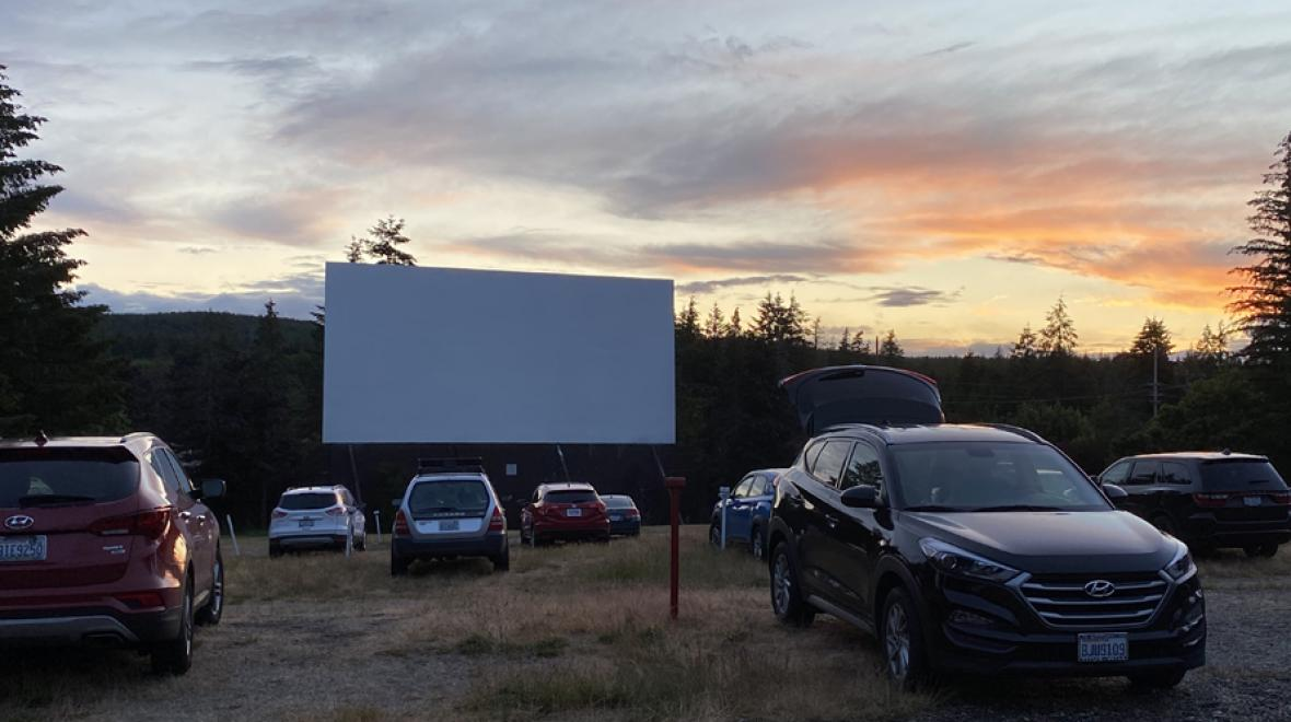 view of cars parked at a drive-in at sunset