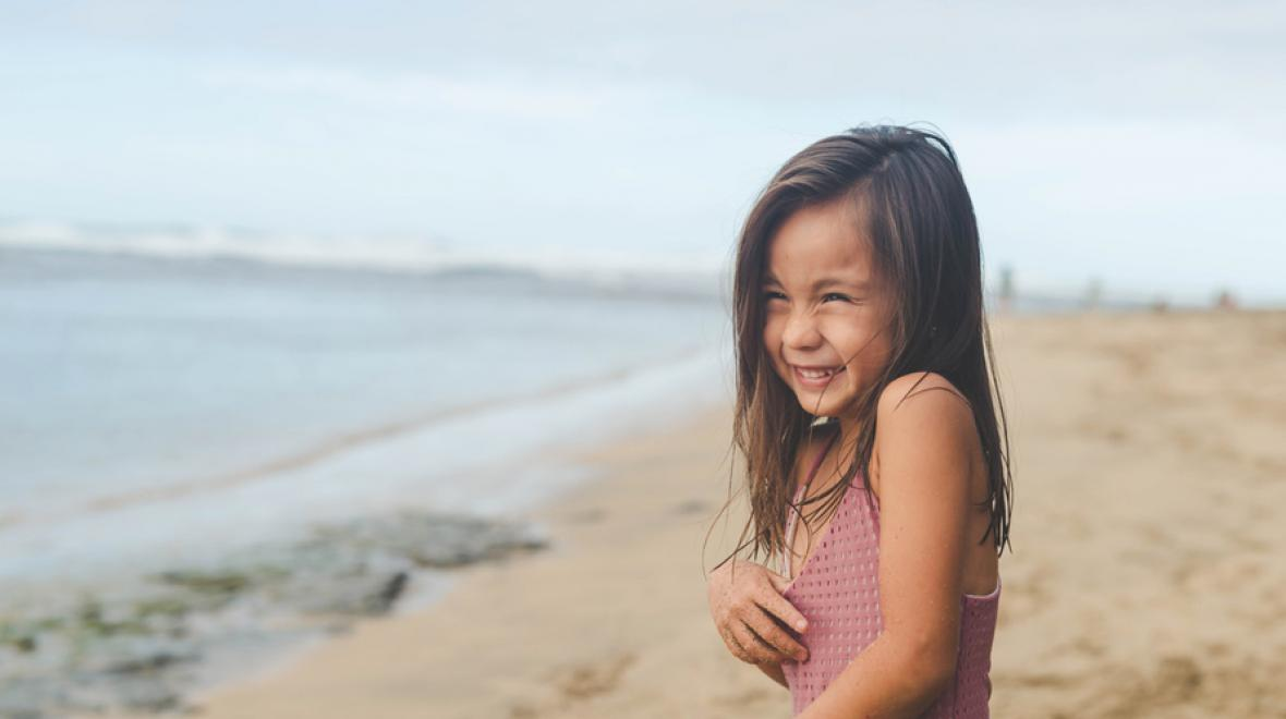 girl giggling on the beach