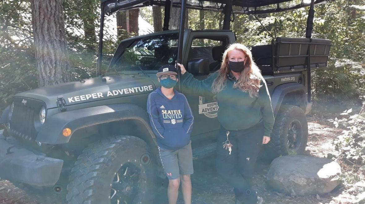 Northwest Trek keeper and tour guide Deanna with the visitor in front of the keeper tour jeep