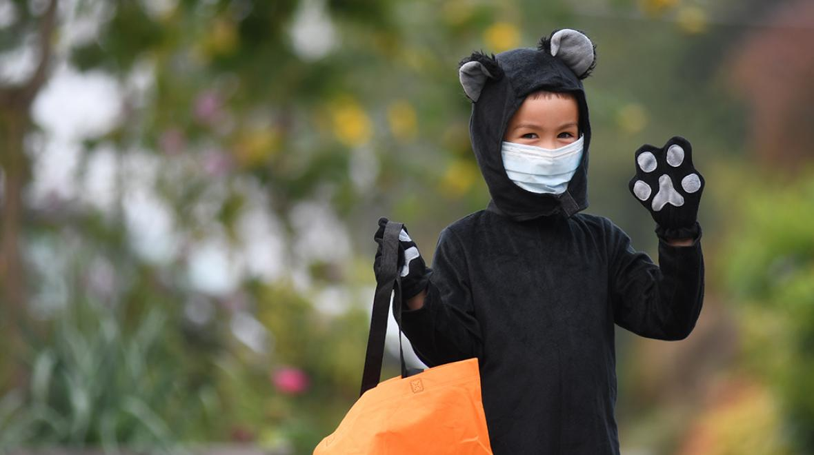 boy wearing a cat costume and mask waving at the camera outdoors Halloween 2020