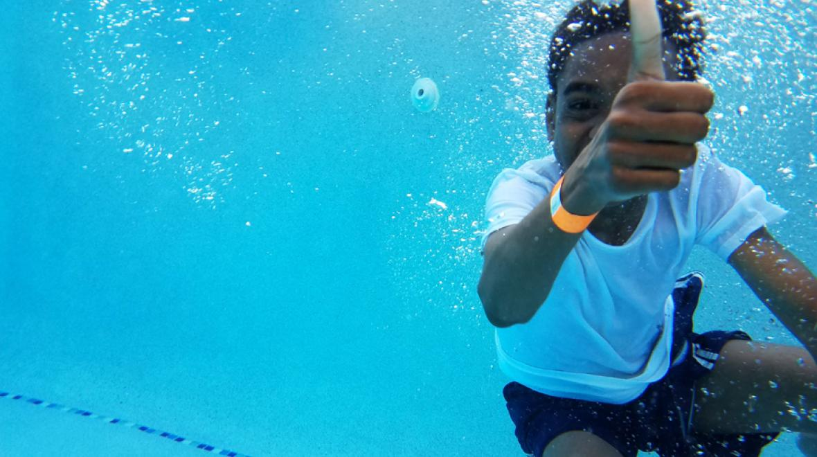boy underwater in the pool giving a thumbs up