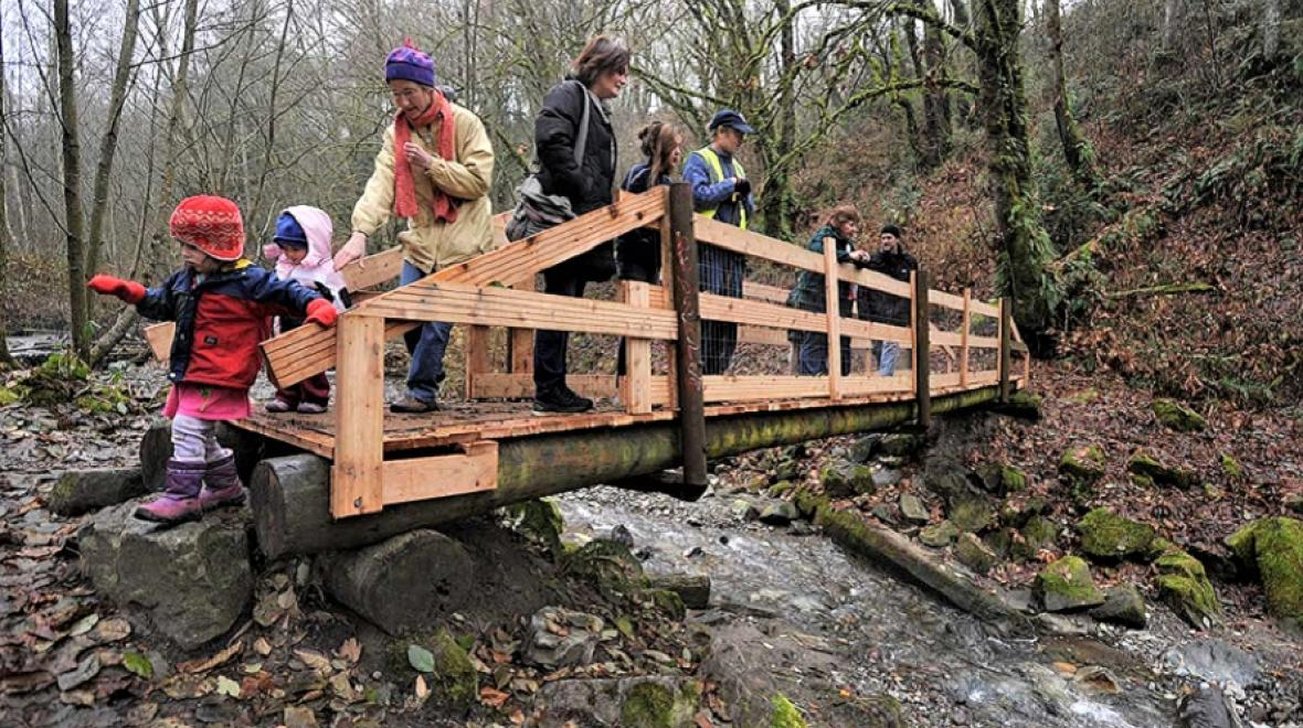 Families on bridge over Swan Creek in Tacoma best fall hikes with kids south puget sound