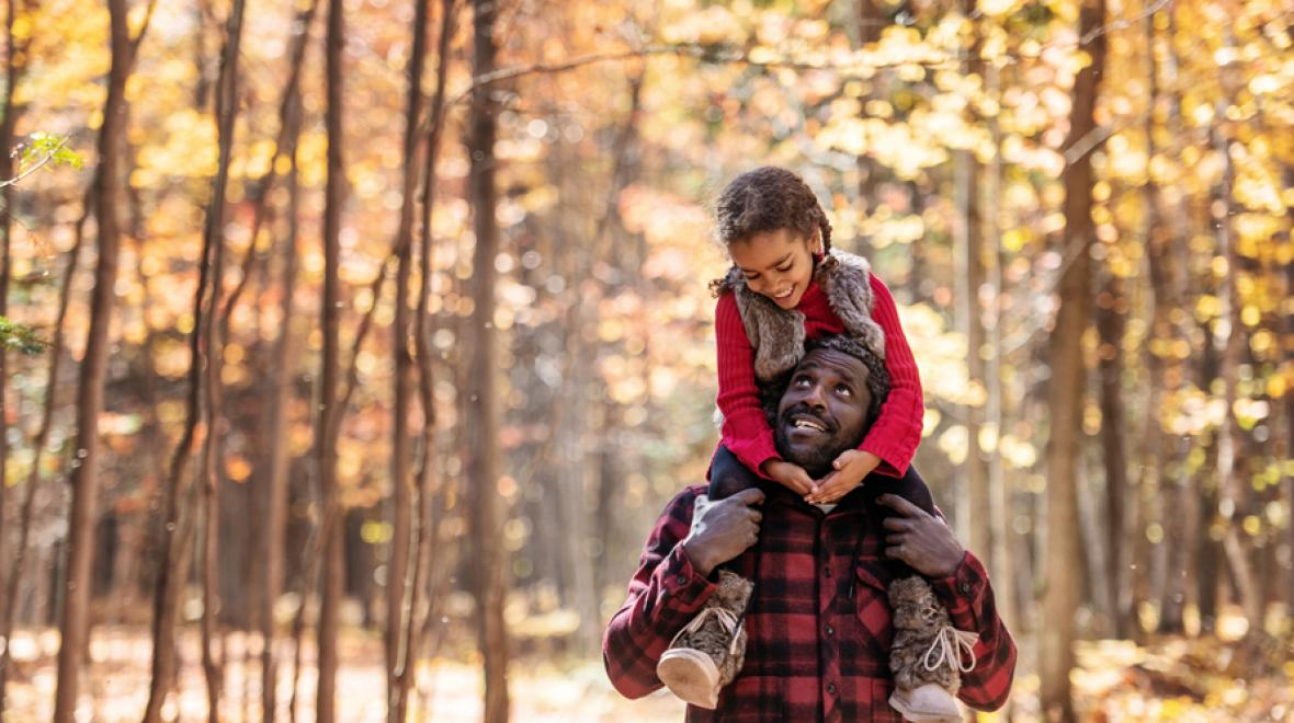 father with daughter on his shoulders surrounded by trees with fall colors