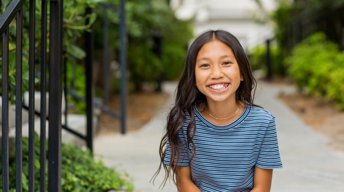 girl standing outside on a sidewalk smiling