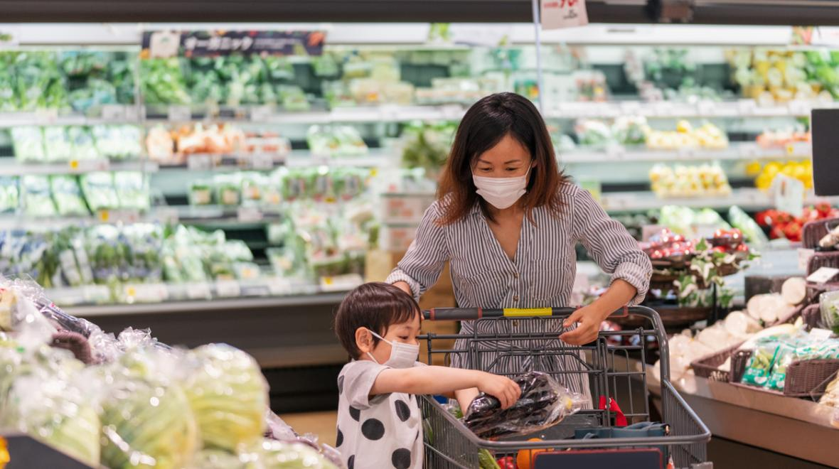 masked mother and child at grocery store