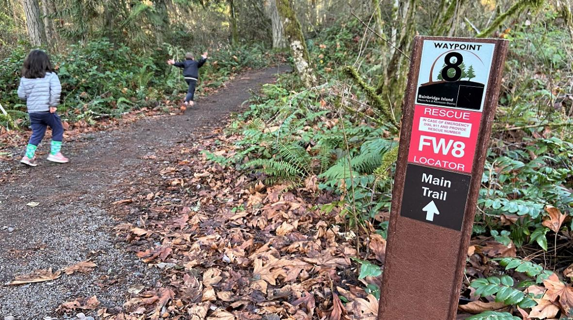 Kids on a hiking trail on Bainbridge Island passing a waypoint rescue finder sign