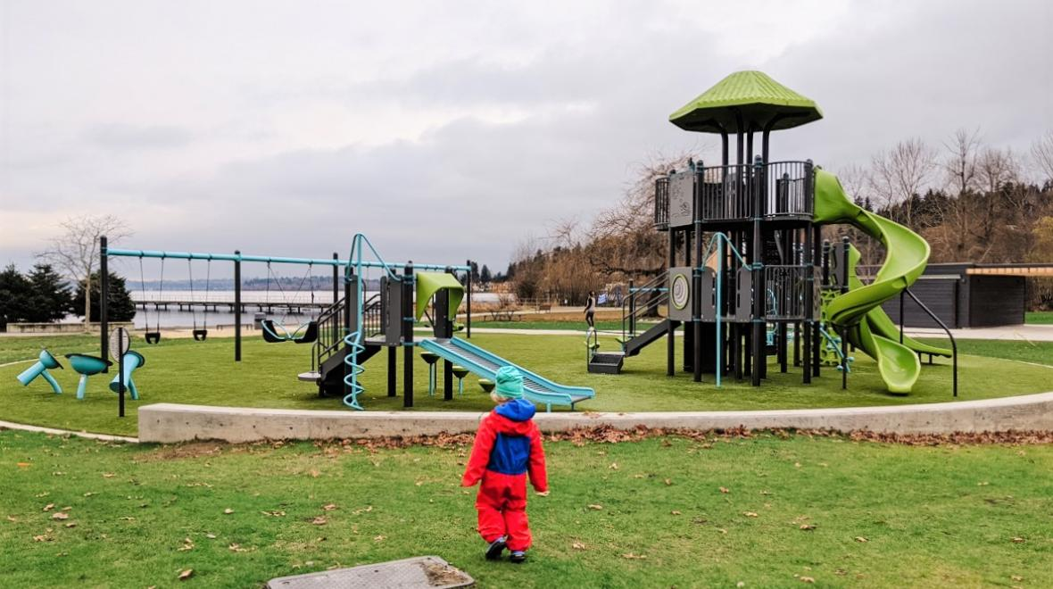 little kid in a ret jacket at Juanita Beach Park Playground on a gray rainy winter day