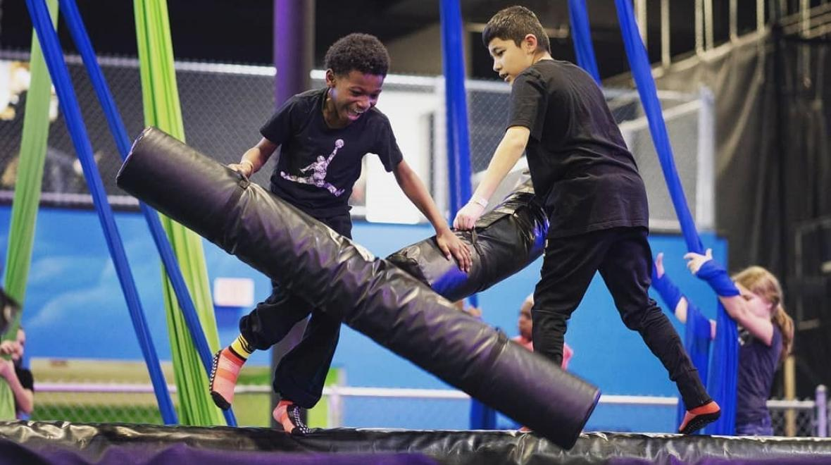 Two boys on foam covered balance beam battling with foam bars at Defy Seattle trampoline park in Tukwila Washington what's open for Seattle area families winter 2021