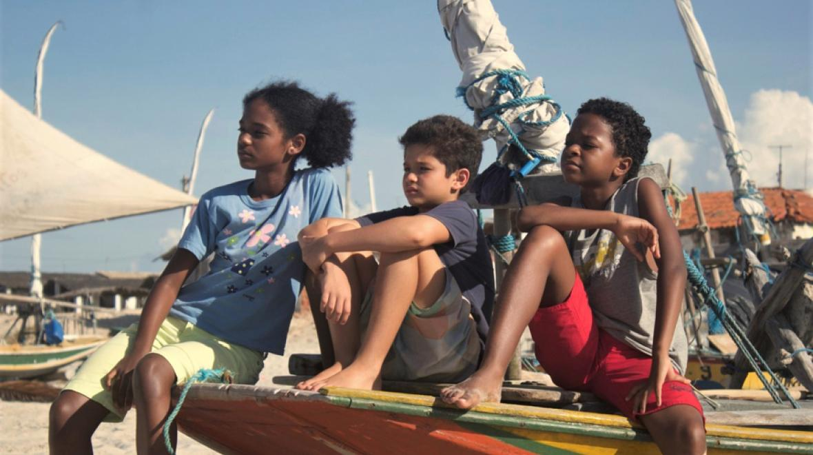 young warriors 1 childrens film festival still image of three kids sitting on the prow of a small boat on the beach