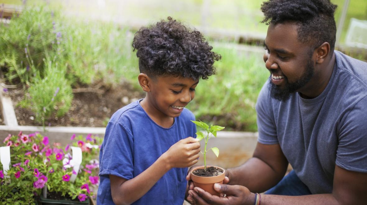 black father and son in the garden crouched over a flower pot