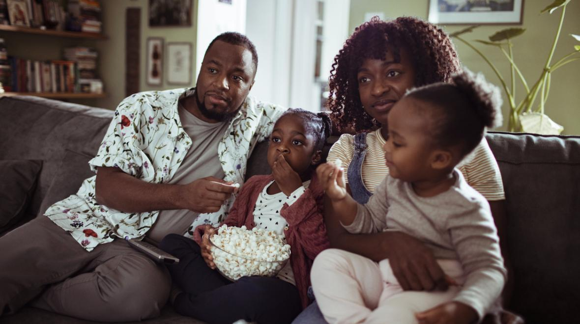family of four sitting on the couch with popcorn