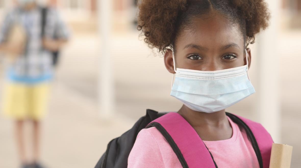 Young girl wearing a surgical mask and a school backpack