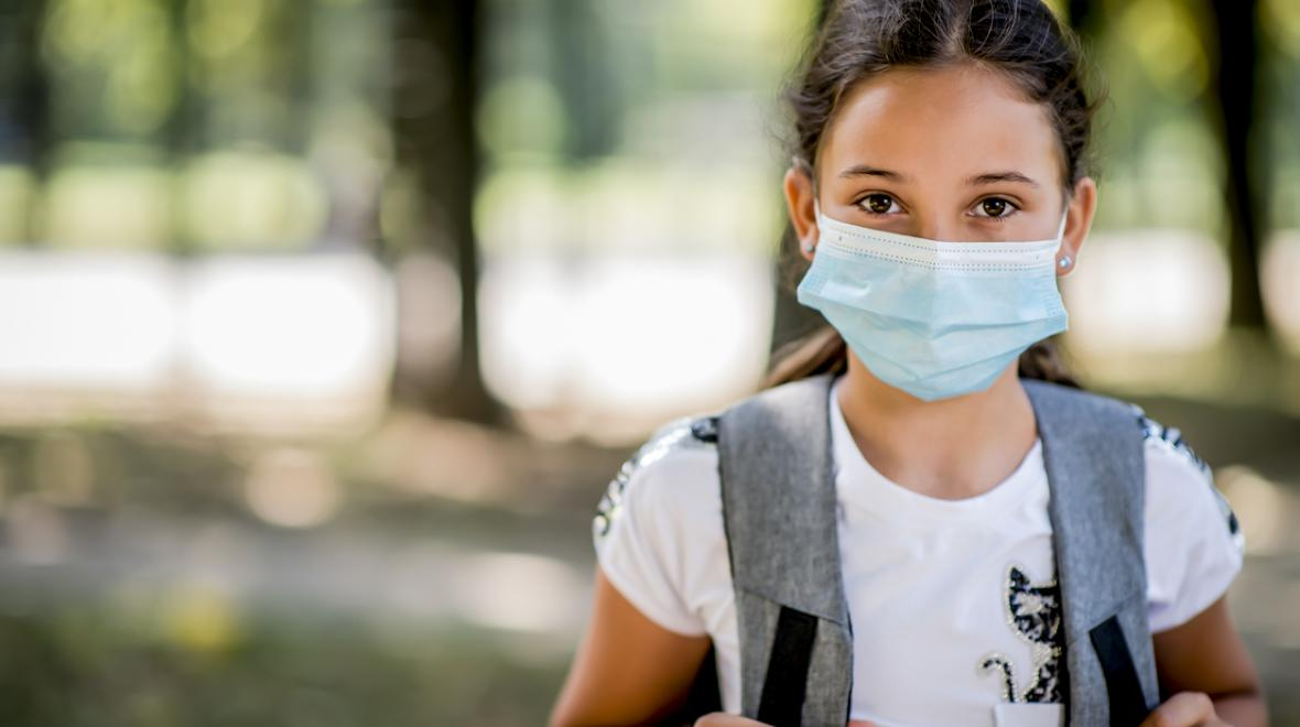 worried girl wearing a backpack and mask